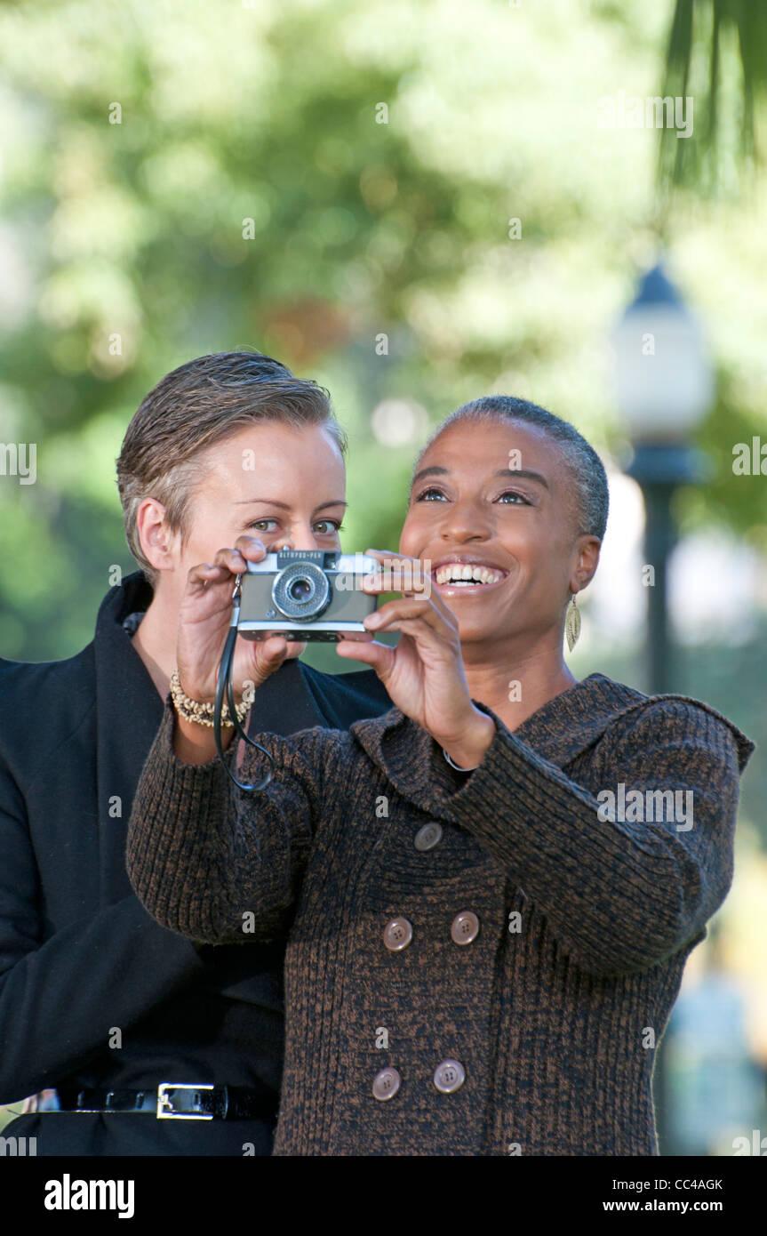Deux femme d'âge moyen s'amuser dans le parc de prendre des photos Photo Stock