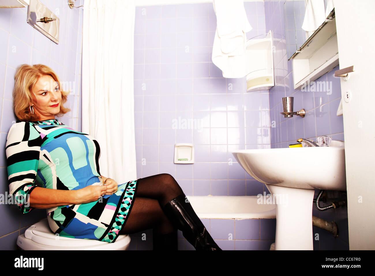 Vintage / femme / shoot rétro fatale. Femme assise sur la toilette. Photo Stock