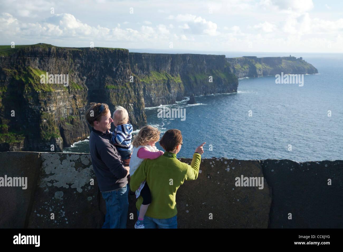 Famille en profitant de la vue sur les falaises de Moher, le Burren, comté de Clare, Irlande. Photo Stock