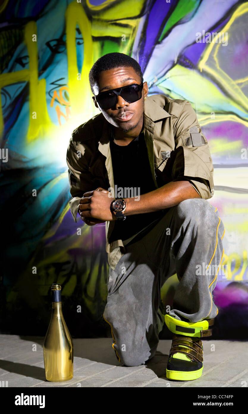 Les jeunes afro-american homme assis en face de mur coloré Photo Stock