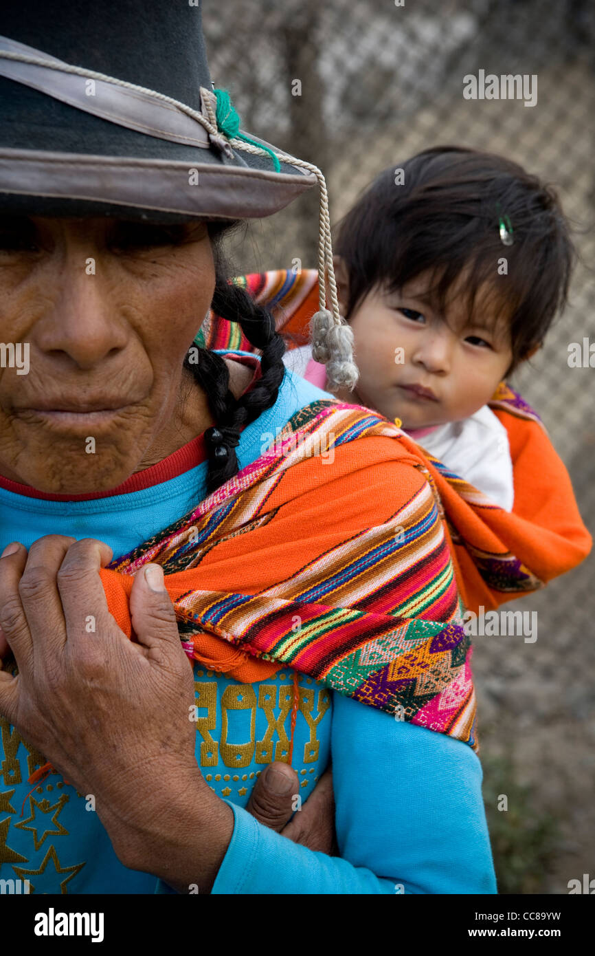 Une femme porte un bébé sur son dos dans un bidonville de Lima, Pérou, Amérique du Sud. Photo Stock
