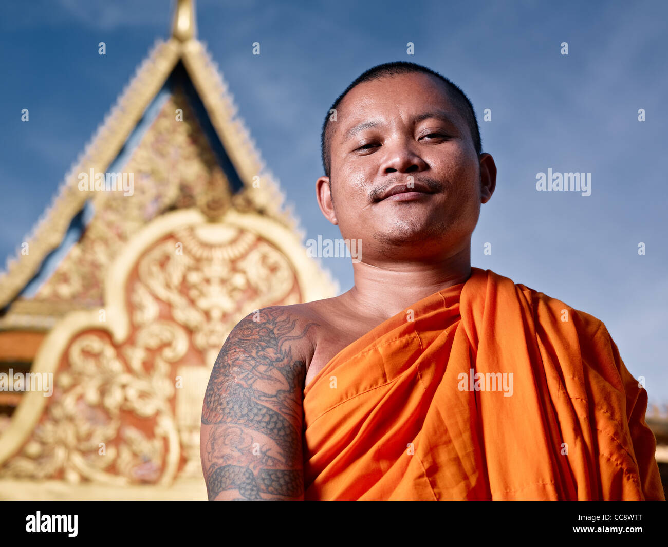 Mid adult Asian monk smiling at camera au monastère bouddhiste, Phnom Penh, Cambodge, Asie. Low angle Photo Stock