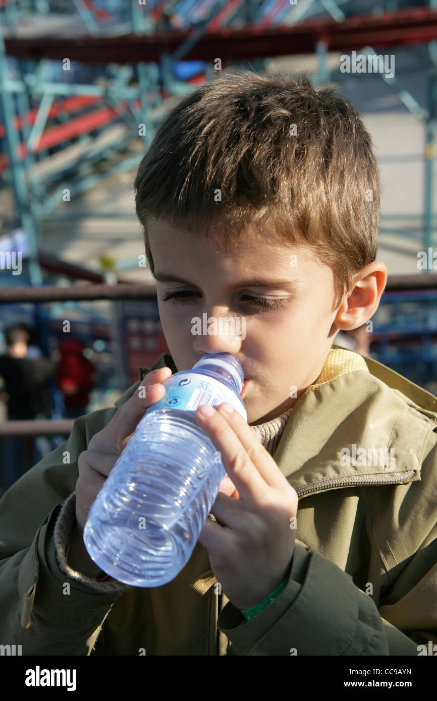 Un garçon de six ans, l'eau potable à partir d'une bouteille. Banque D'Images