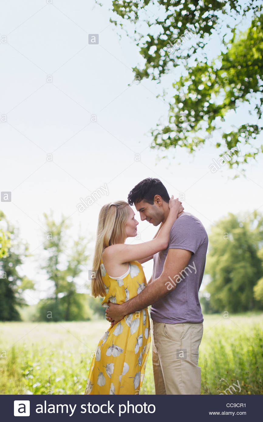 Jeune couple hugging romantically in rural field Photo Stock