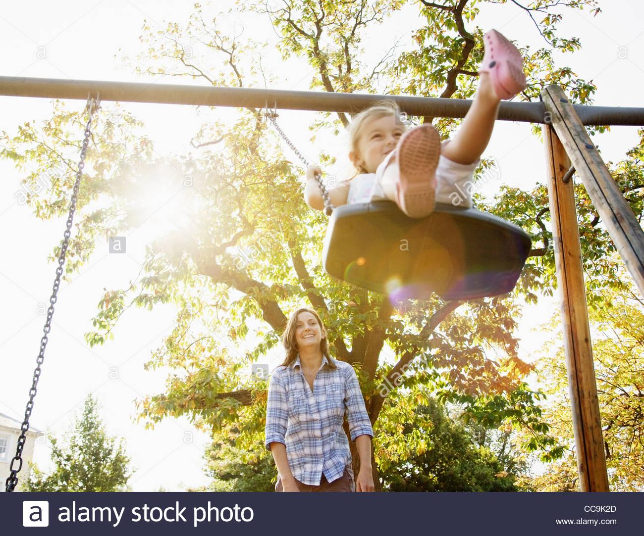 Mère fille poussant sur swing in sunny park Photo Stock