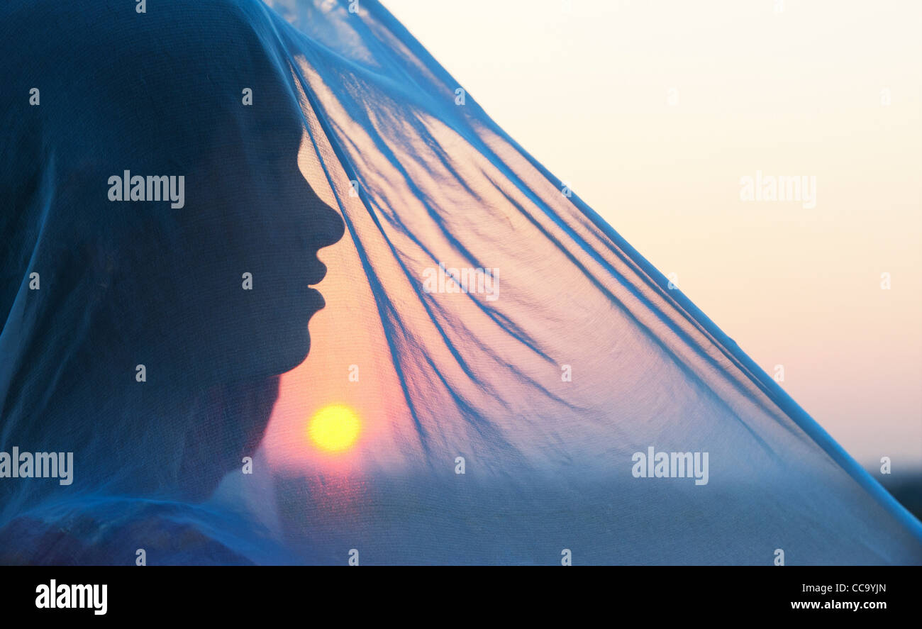 Indian girl et voile au coucher du soleil. Silhouette. L'Andhra Pradesh, Inde Photo Stock