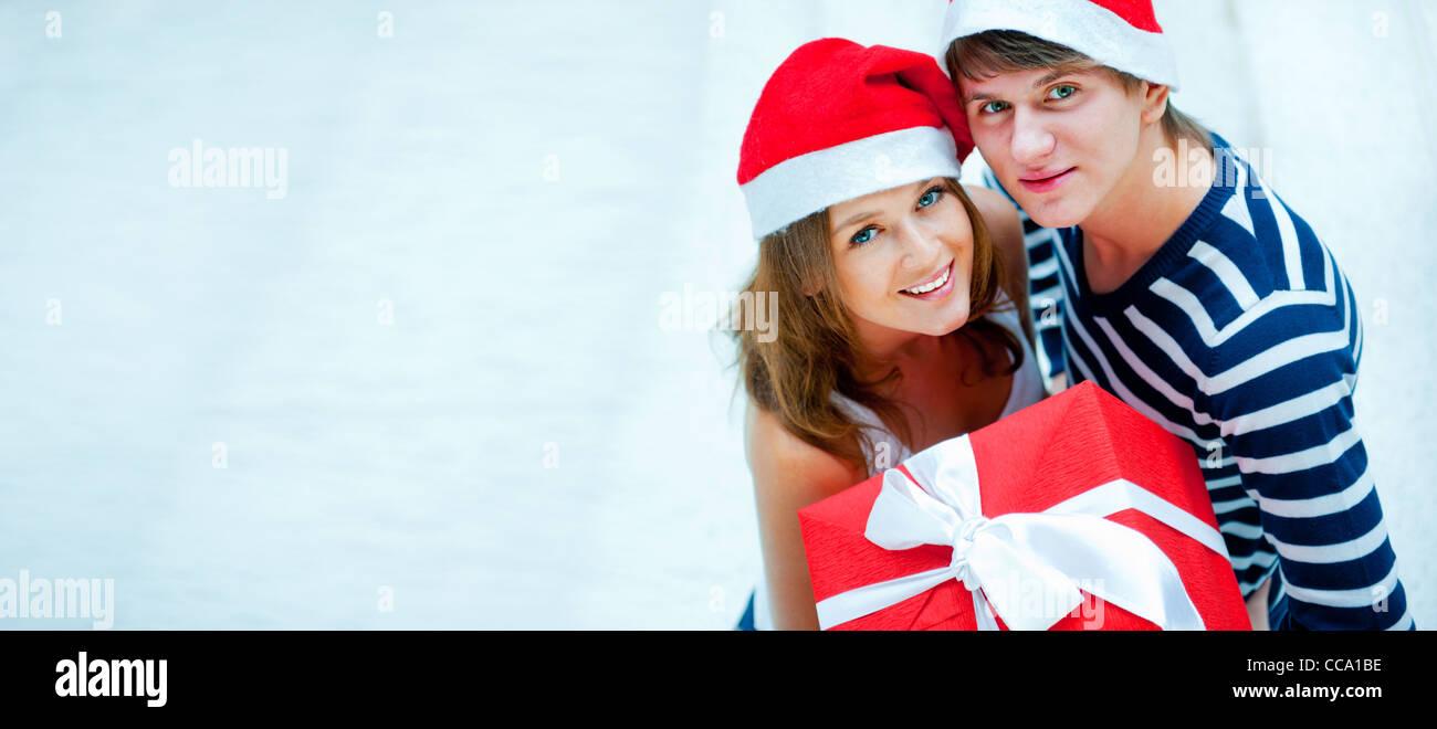 Portrait of young Pretty woman wearing Santa Claus à l'intérieur des chapeaux et d'étreindre. Holding big red box Banque D'Images
