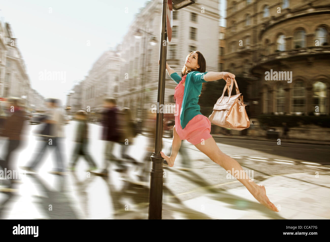 Mid adult woman in robe rose sautant à travers les rues de la ville Photo Stock