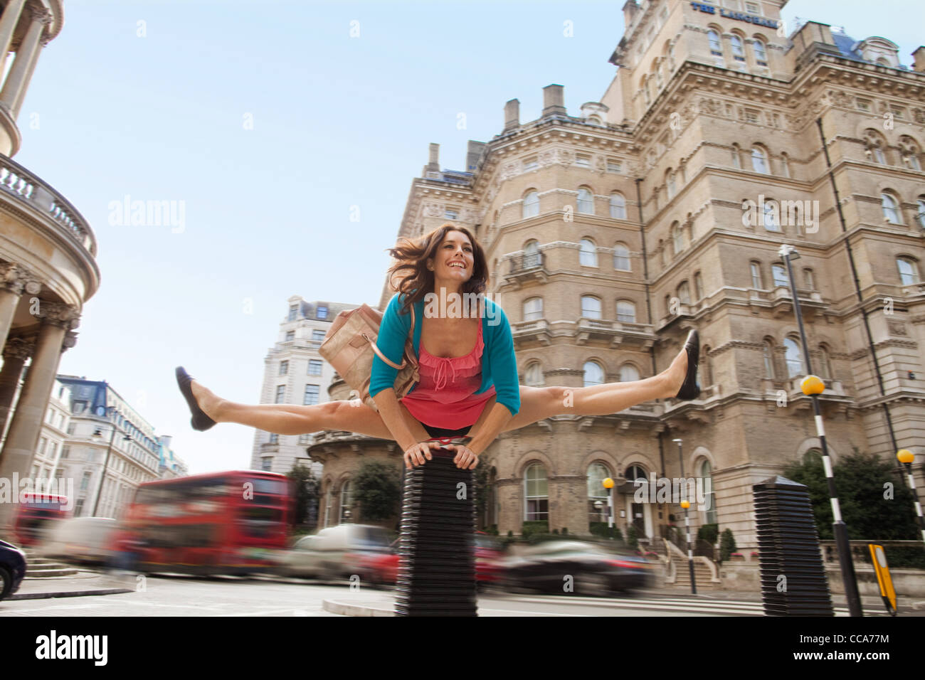 Mid adult woman in pink dress leapfrogging par city street Photo Stock
