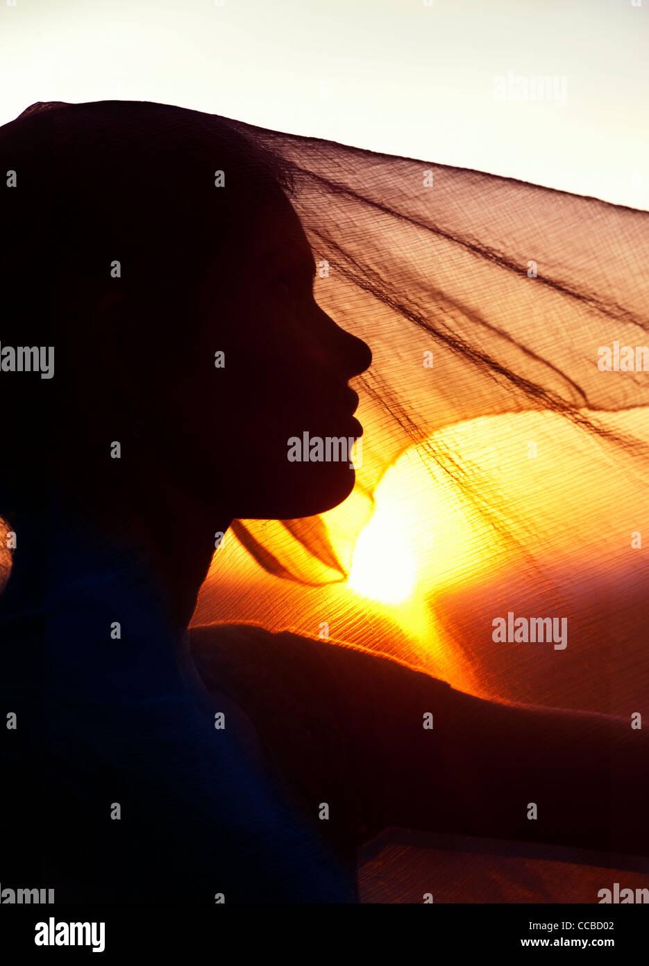 Indian girl et voile au coucher du soleil. Silhouette. L'Andhra Pradesh, Inde Banque D'Images