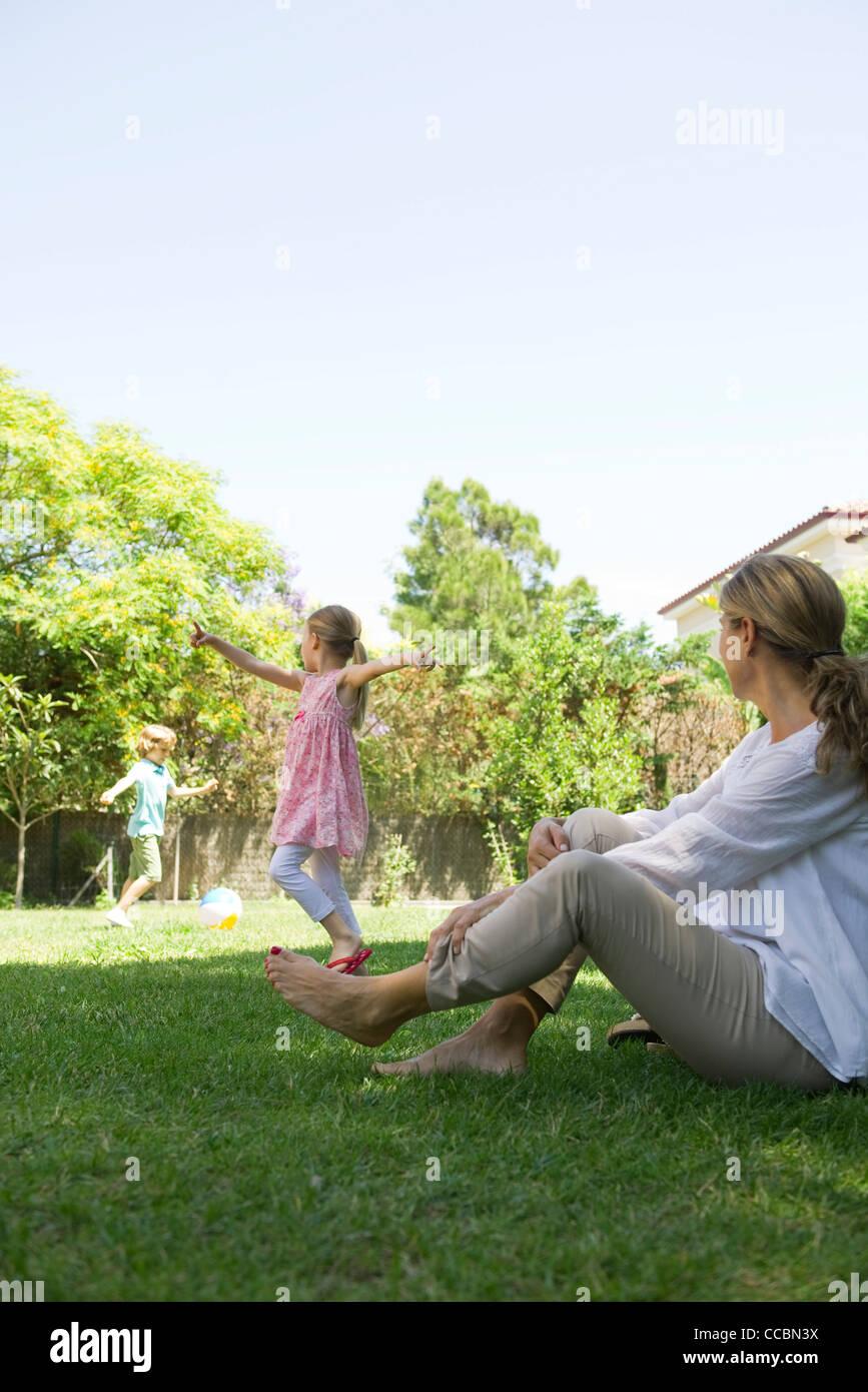Grand-mère assise sur l'herbe en regardant ses petits-enfants jouer Photo Stock