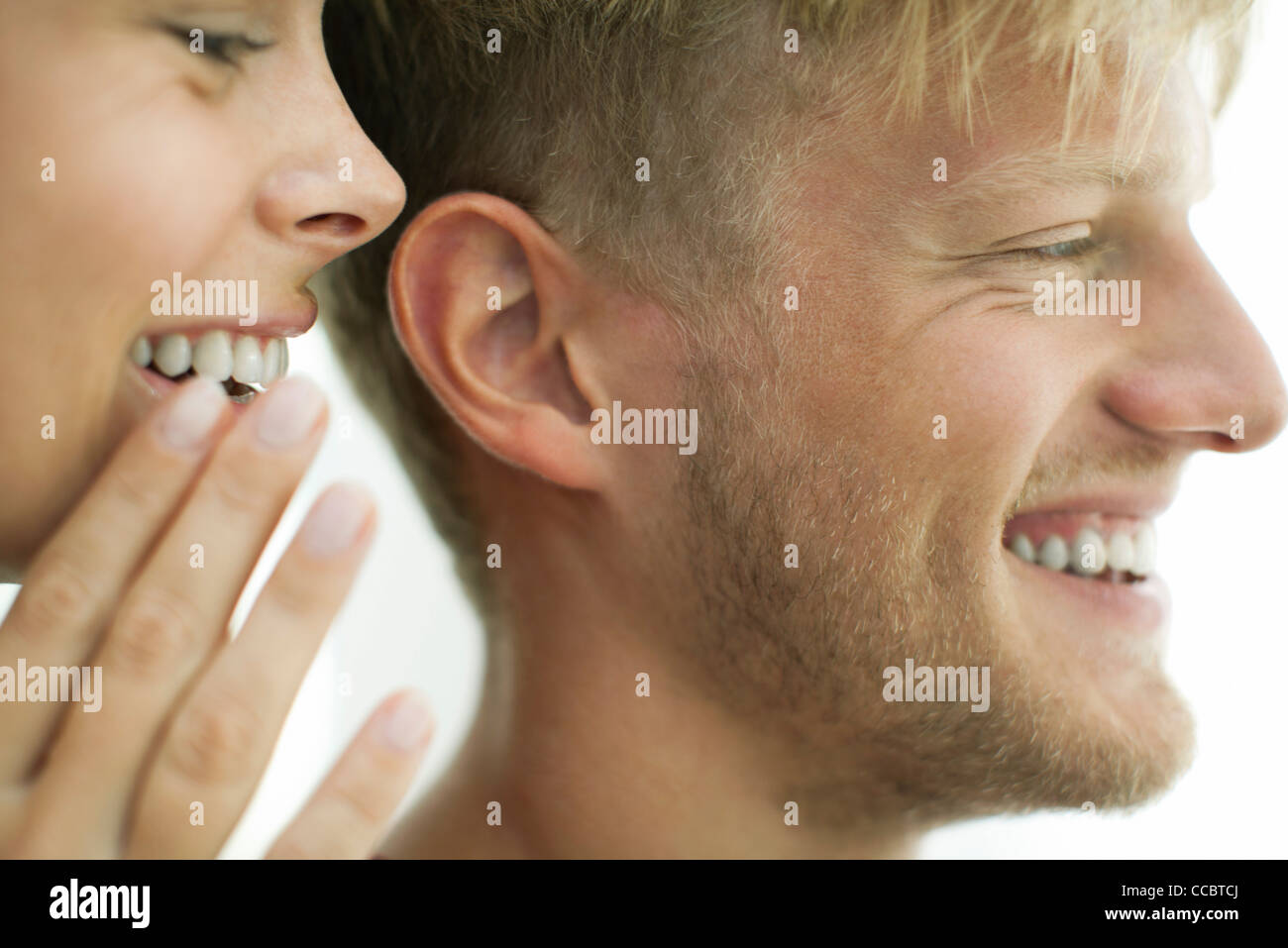 Woman Whispering in man's ear, close-up Photo Stock