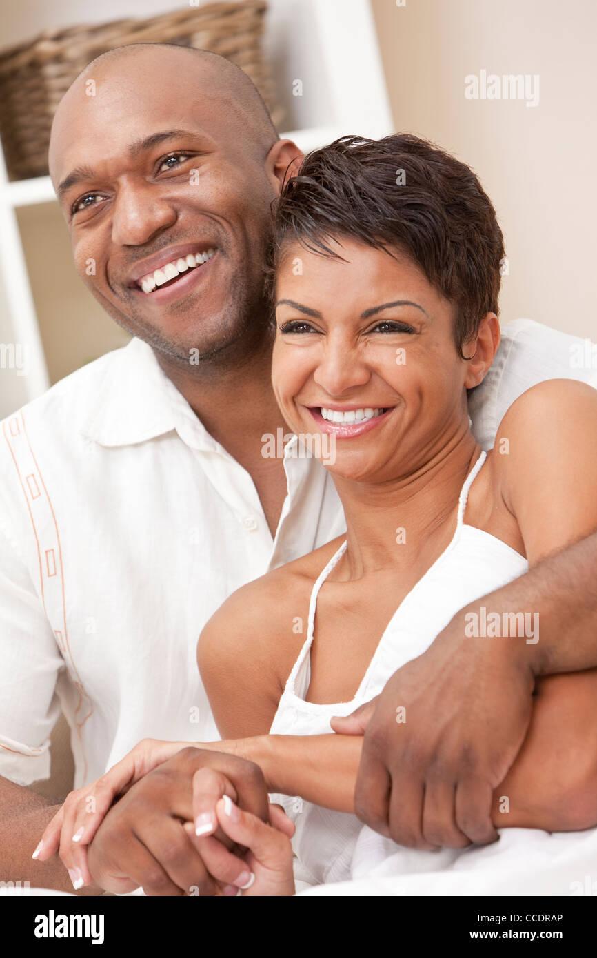 Une happy African American man and woman couple dans la trentaine assis ensemble, à la maison en souriant. Photo Stock