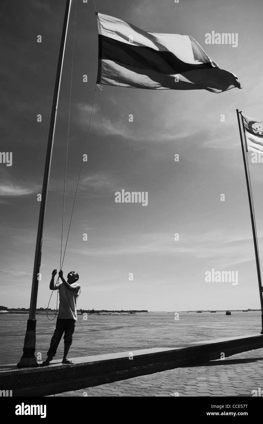 Un homme soulève des drapeaux du Riverside à Phnom Penh, Cambodge Photo Stock