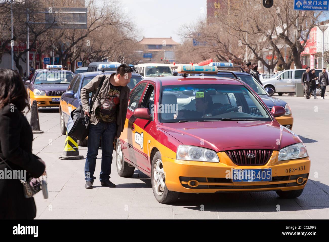 Un homme parle au conducteur d'un taxi dans les rues de Beijing, Chine Photo Stock