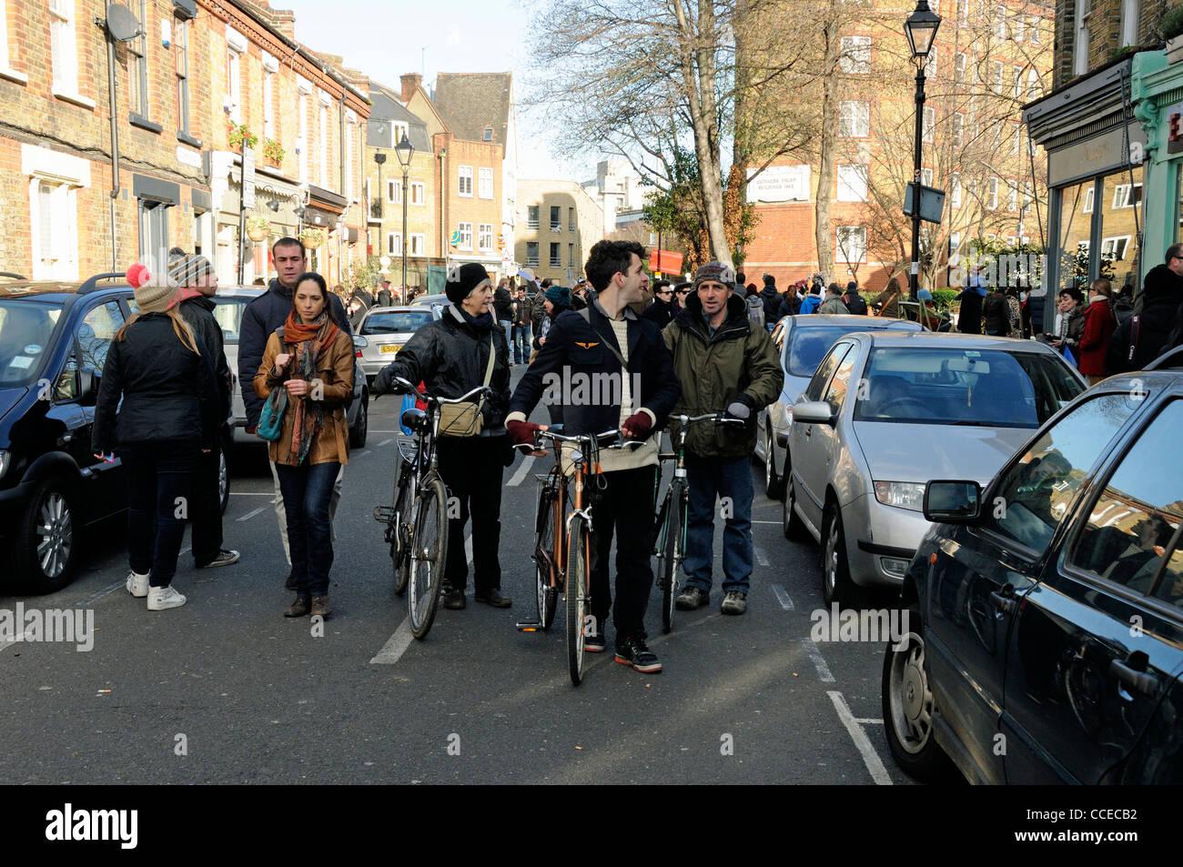Les cyclistes poussant leurs vélos dans Columbia Road Flower Market Tower Hamlets London England UK Photo Stock