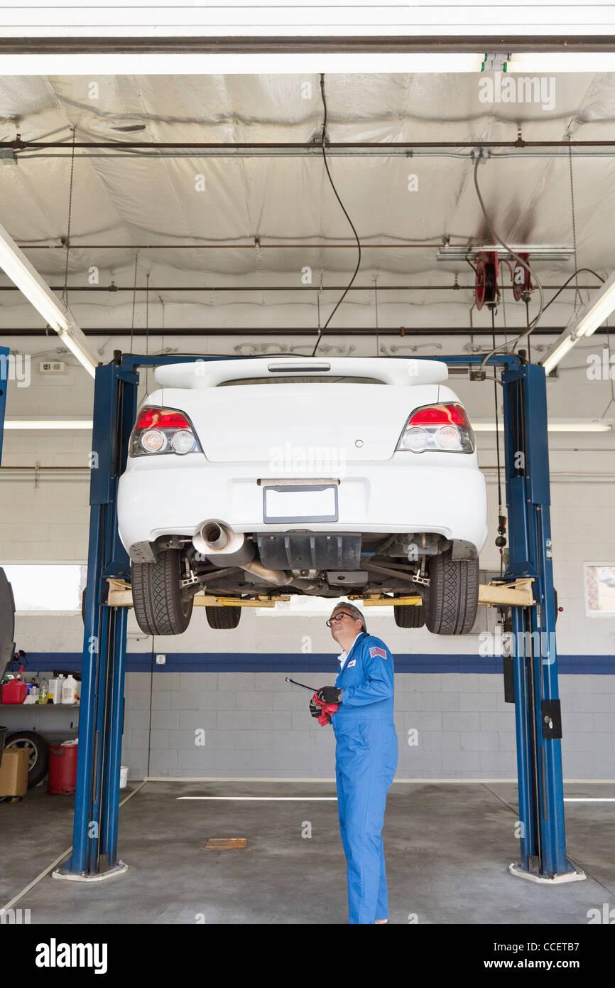 Sous contrôle de mécanicien automobile sur un pont élévateur Photo Stock