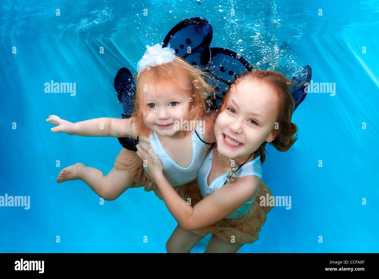 Deux jeunes filles avec des ailes de papillon de sourire et s'amuser sous l'eau Photo Stock