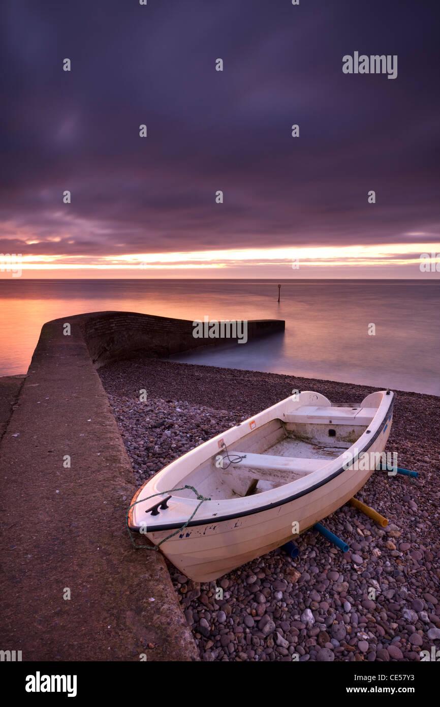 Bateau de pêche sur la plage de Sidmouth, à l'aube, Cornwall, Devon, Angleterre. L'hiver (Janvier) Photo Stock
