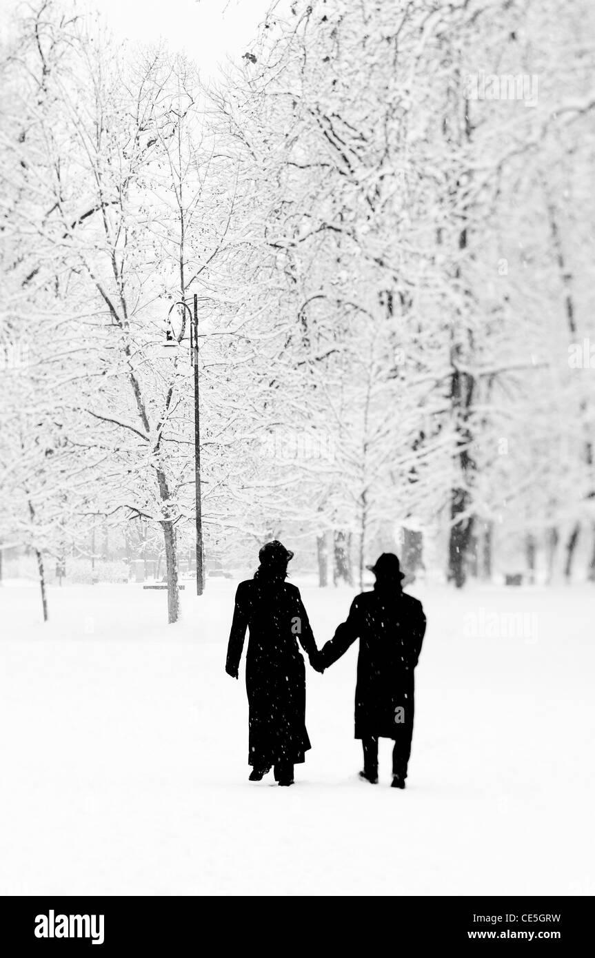 Couple dans un parc public sous la neige Photo Stock