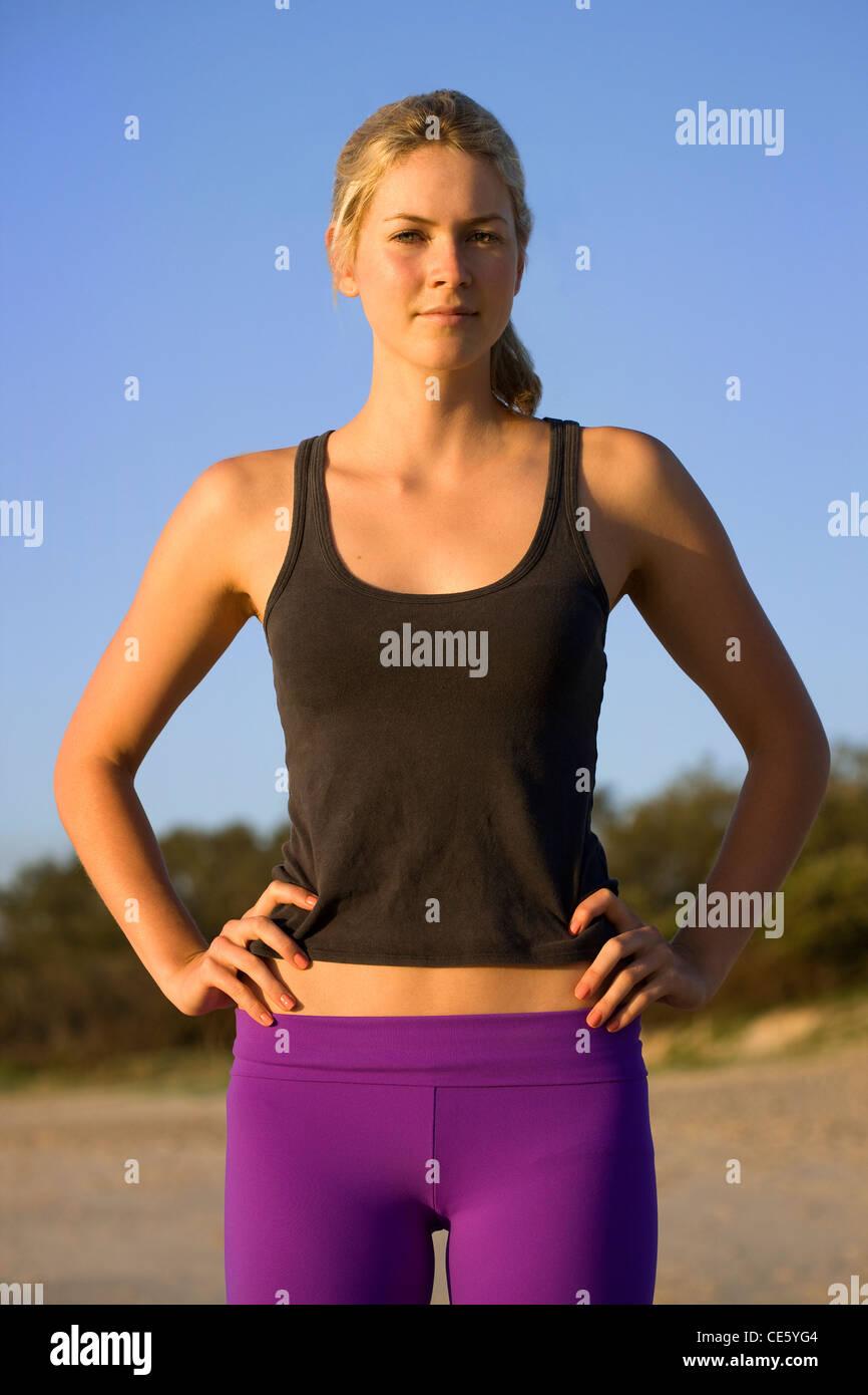 Jeune femme athlétique avec les mains sur les hanches Photo Stock