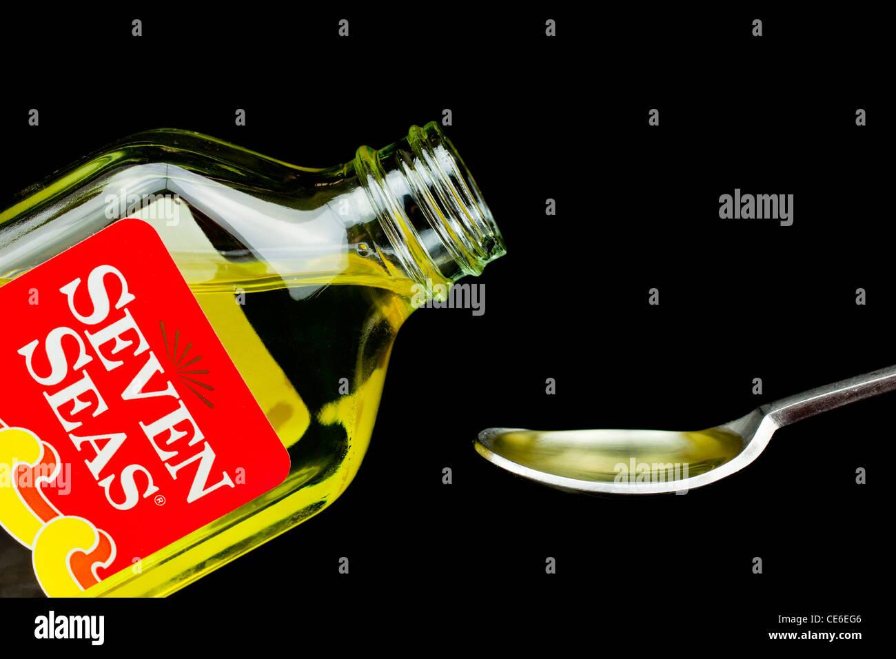 Sept Mers l'huile de foie de morue liquide versé sur une cuillère Photo Stock