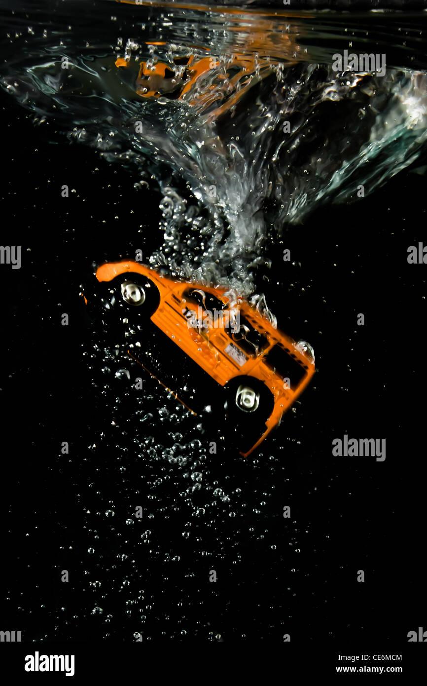 Le moment de l'immersion pour un taxi orange, bulles, vitesse, réflexions sur la surface du liquide et Photo Stock