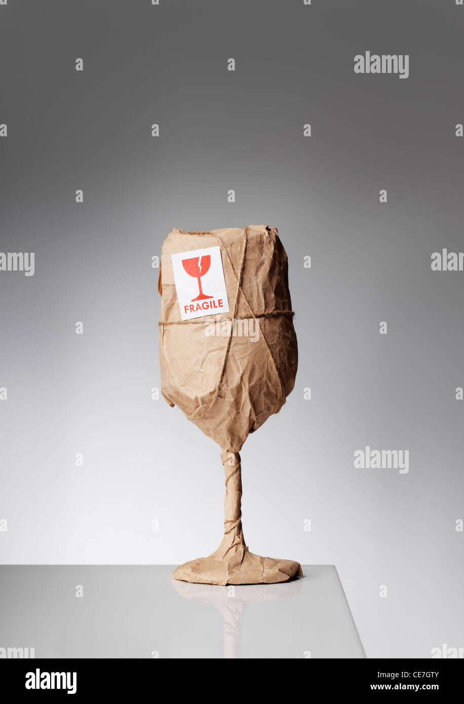 De toute évidence, un objet fragile enveloppée dans du papier et avec un autocollant 'fragile'. Photo Stock