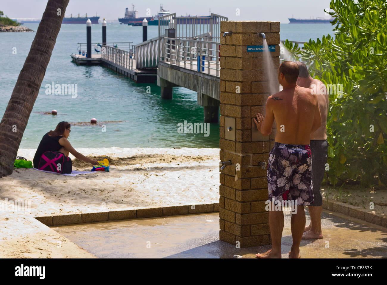 Deux hommes prendre douche sur la plage à l'île de Sentosa, Singapour. Photo Stock