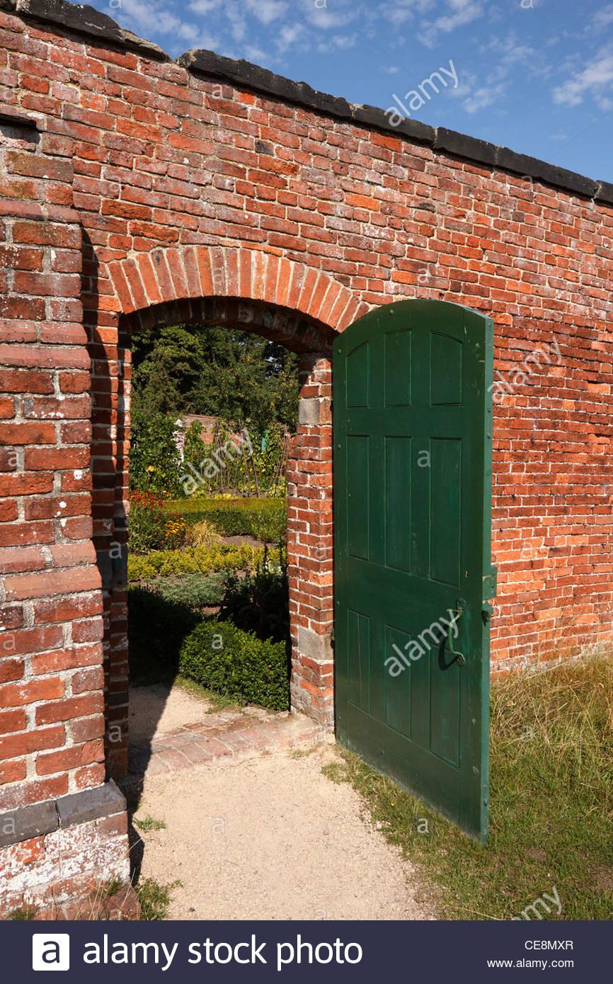 Ouvrez la porte verte dans le mur de brique rouge menant à ...