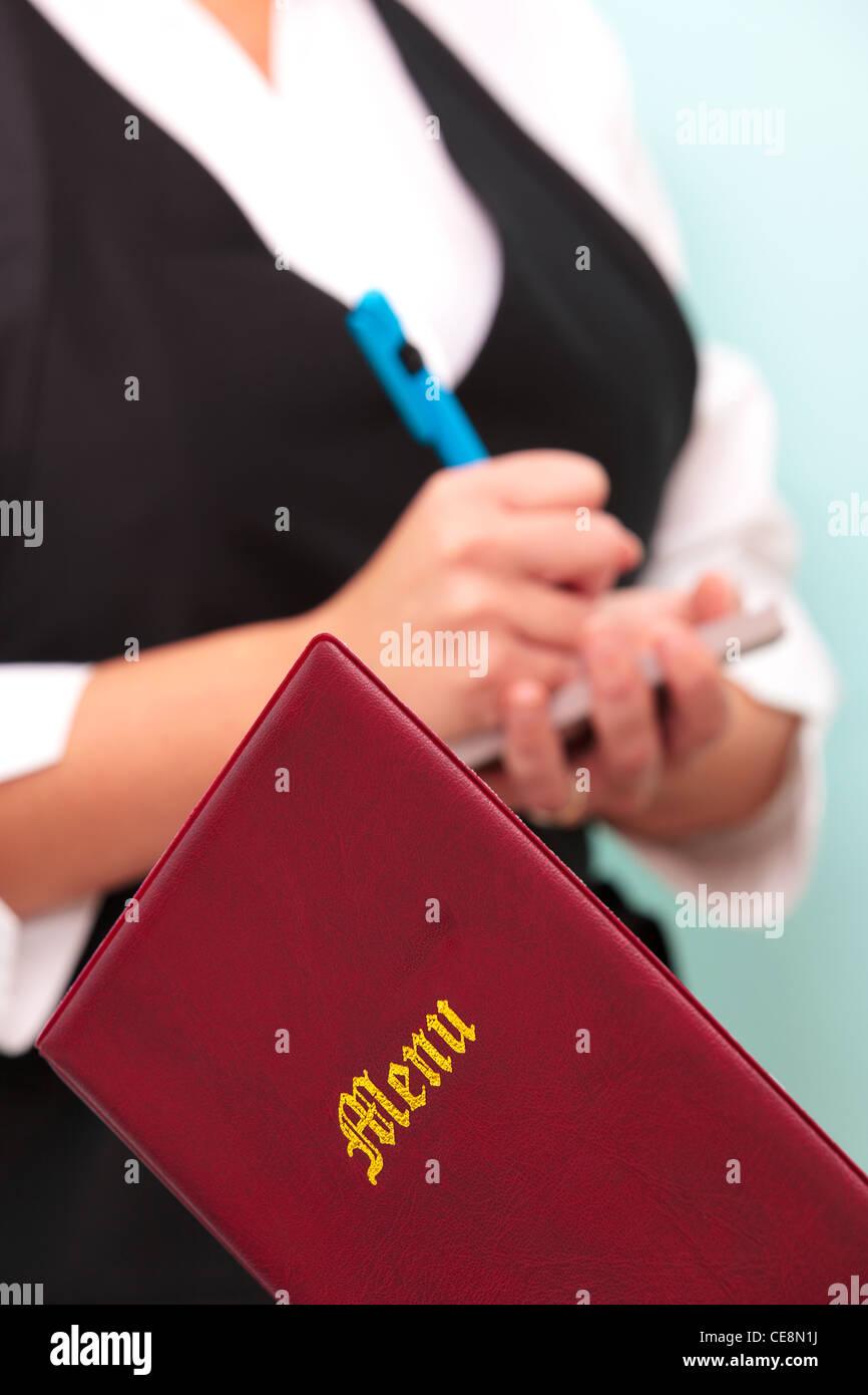 Photo d'un menu de restaurant avec une serveuse méconnaissables dans l'arrière-plan prendre une Photo Stock
