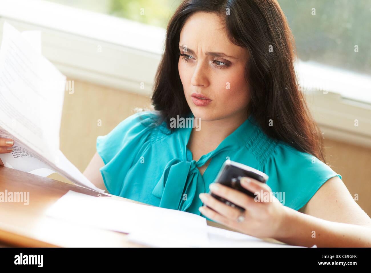 Femme avec des factures de téléphone mobile Photo Stock