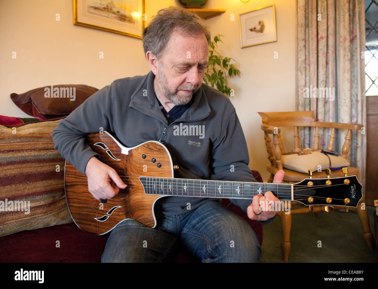 Un homme d'âge moyen de la lecture d'un Taylor guitare acoustique, UK Photo Stock