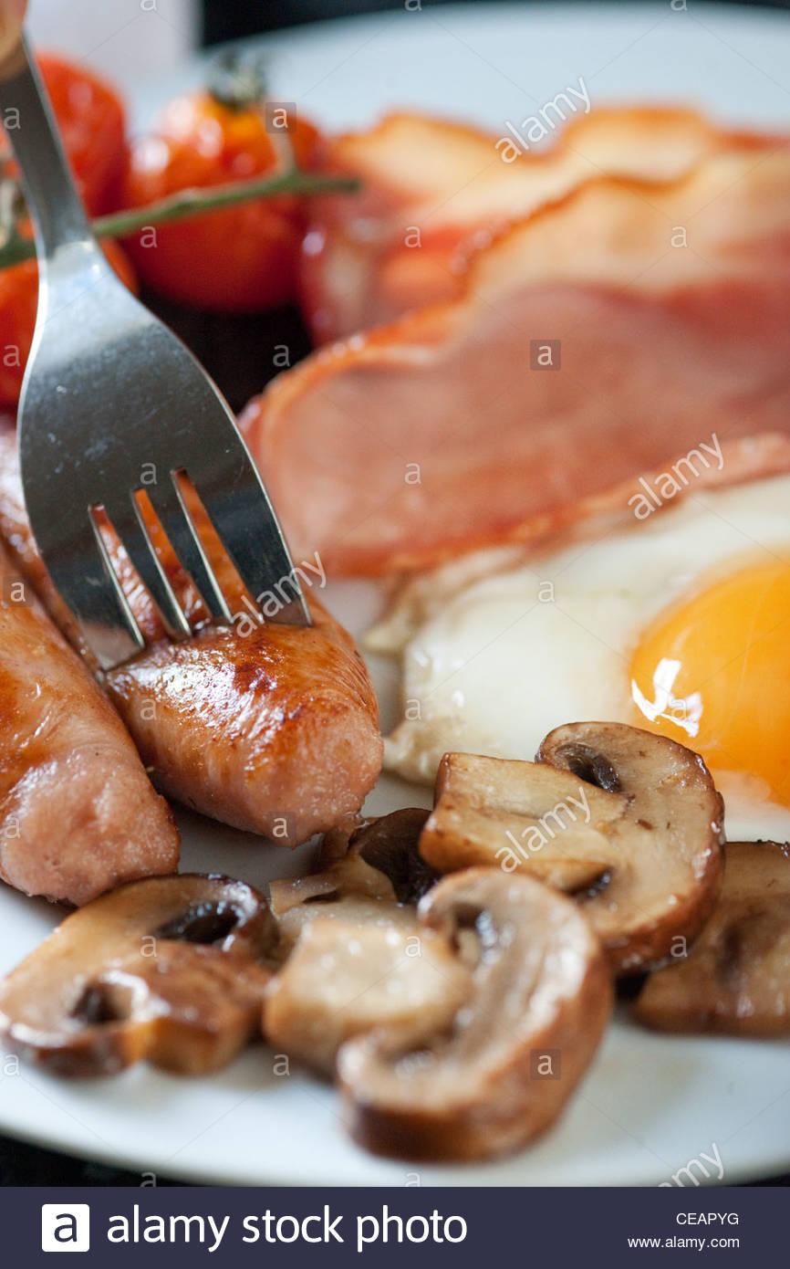 Un petit-déjeuner fraîchement préparé des œufs, bacon, saucisses, tomates et du boudin noir Photo Stock
