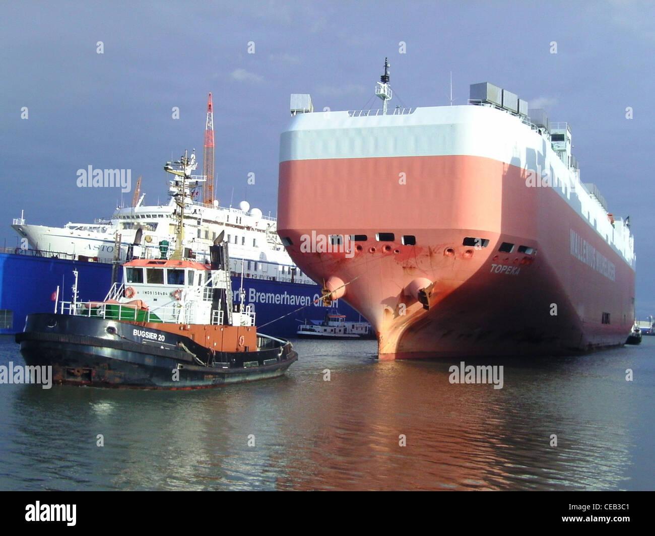 Le remorqueur Bugsier 20 et le porteur de voiture Topeka de manoeuvres dans le port de Bremerhaven Photo Stock