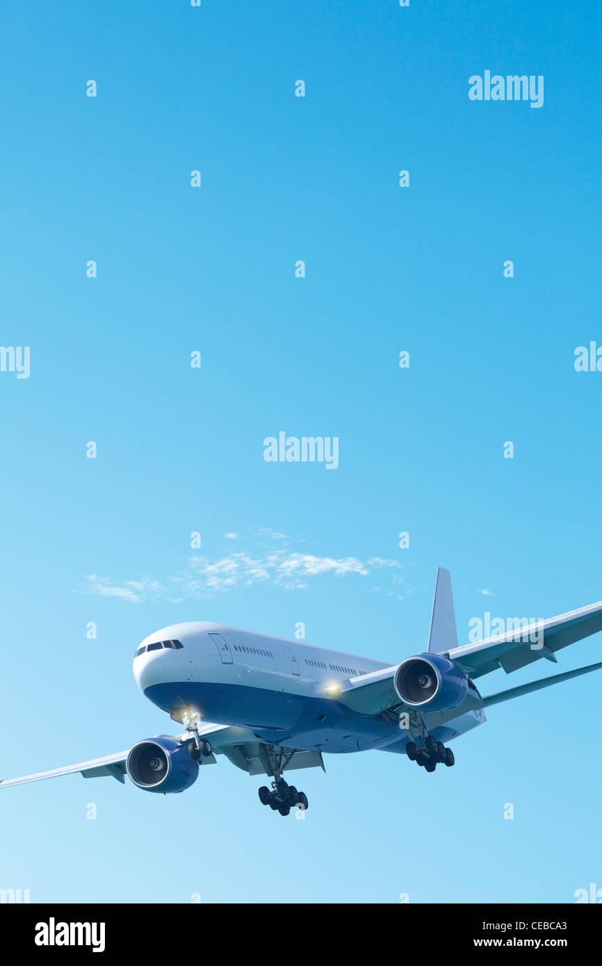 Jet avion dans un ciel bleu clair. Composition verticale. Photo Stock
