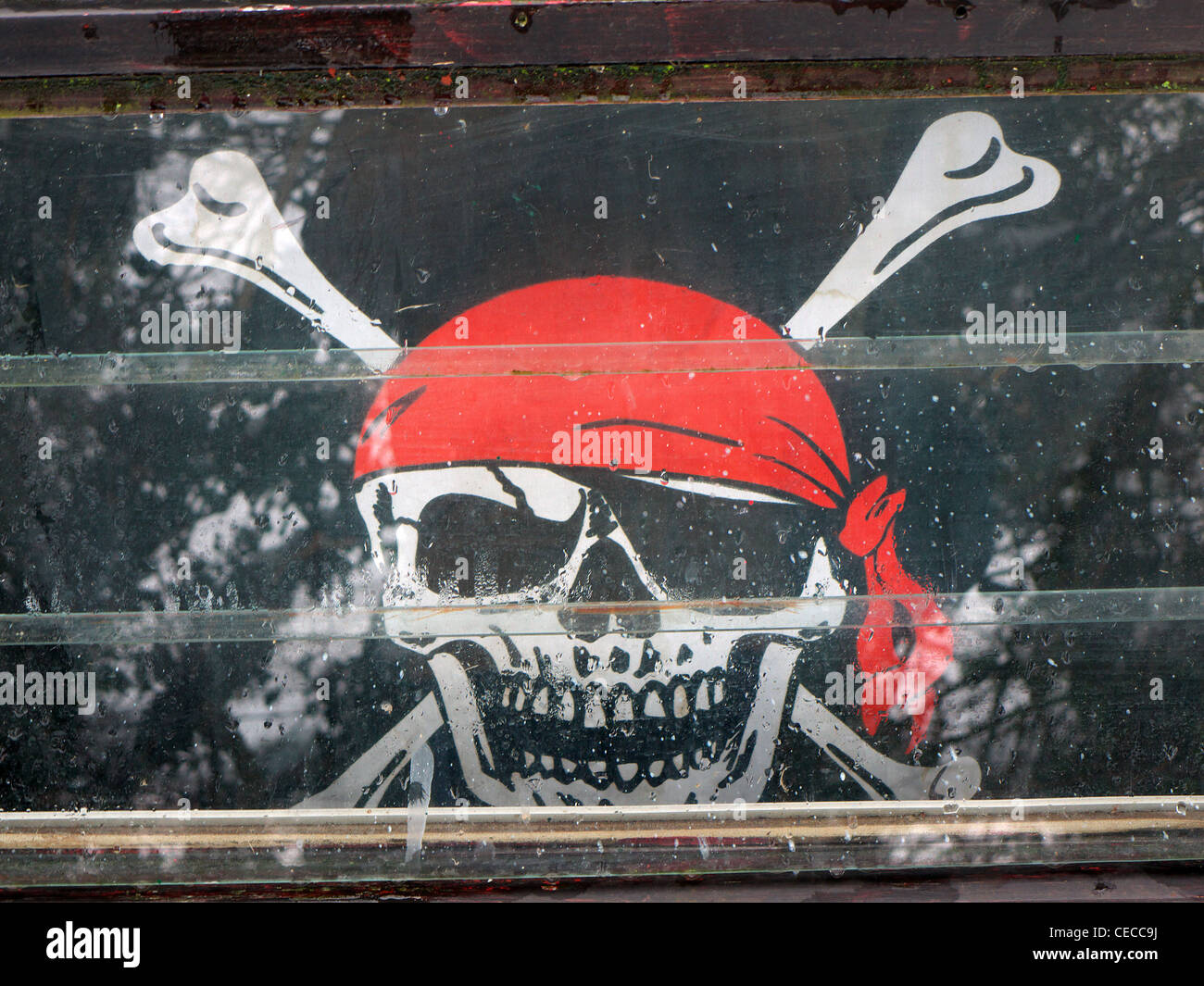 Un Jolly Roger Tête de mort pirates drapeau dans la fenêtre d'un canal barge. Photo Stock