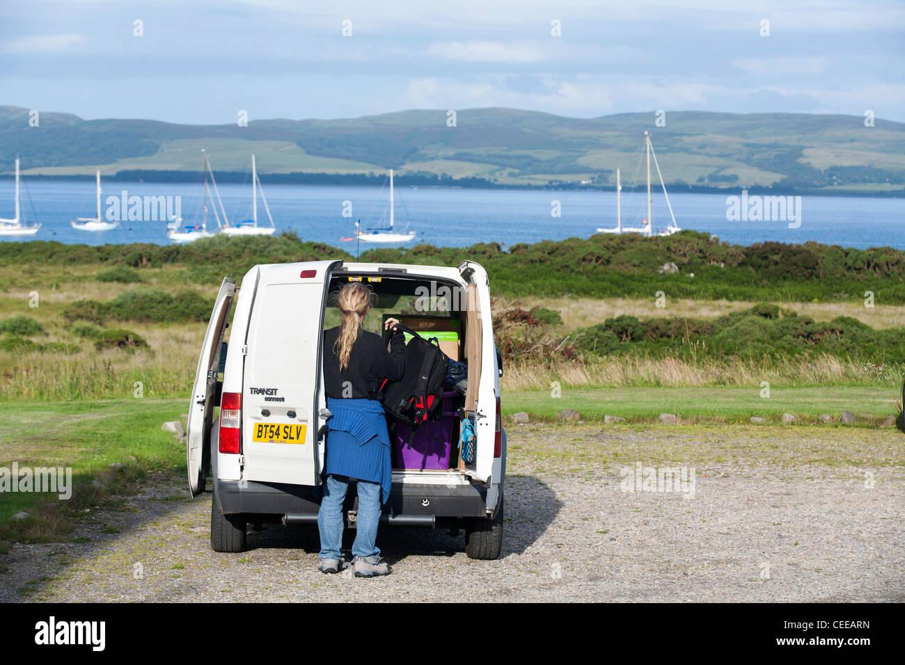 Une femme débarque avec une assurance à partir d'un Ford Transit dans une aire de stationnement en Photo Stock
