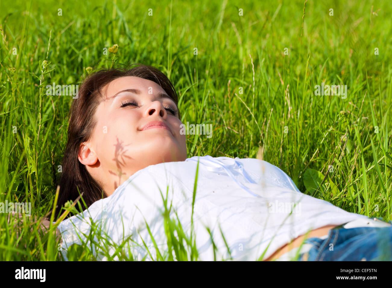 Jeune femme portant sur une pelouse ou prairie en été et est rêver ou dormir Photo Stock