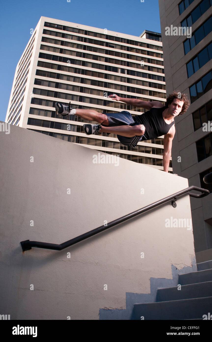 Athlète sautant par dessus un mur urbain Photo Stock