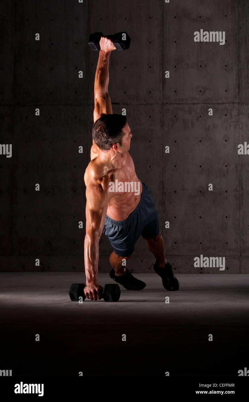Faire de l'athlète poussez se lève sur les poids Photo Stock