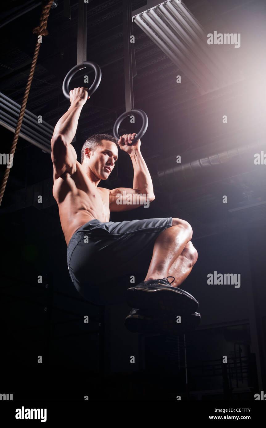 L'homme à l'aide d'anneaux suspendus dans la salle de sport Photo Stock