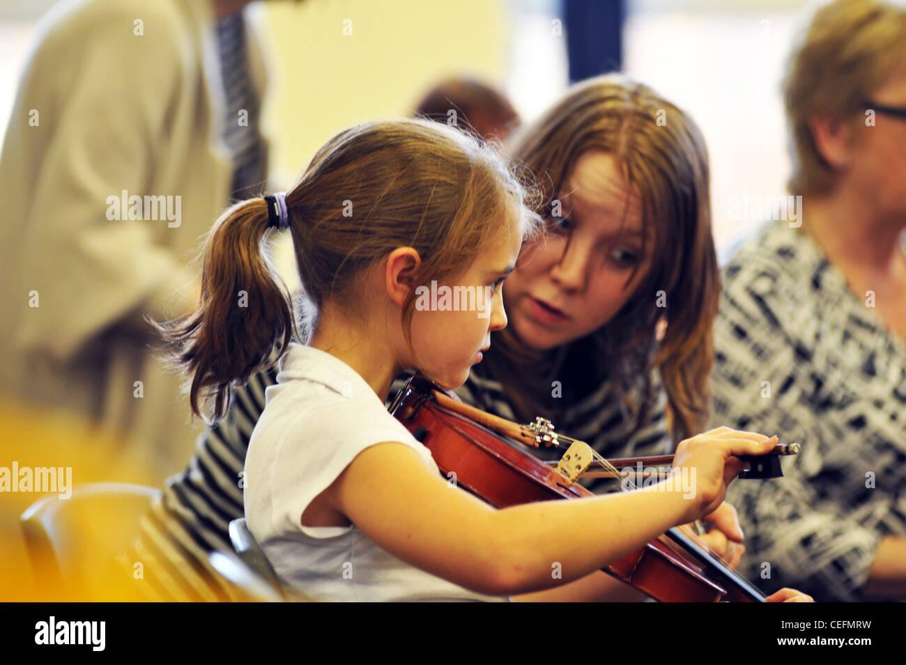 Professeur de musique donne cours de violon à 7 ans, dans une école primaire Photo Stock