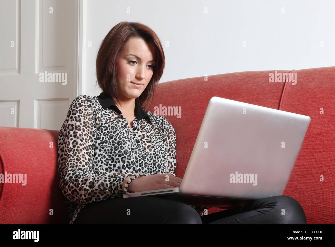 Profil d'une jeune femme seule à l'aide d'un ordinateur portable. Photo Stock