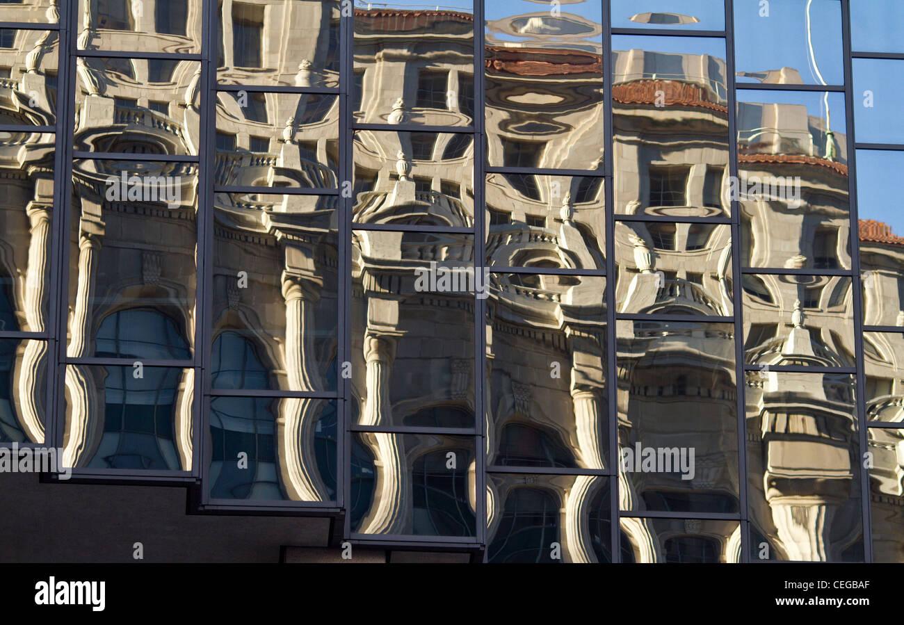 Reflets déformés d'un bâtiment en style néoclassique reflétée dans les fenêtres d'une tour moderne en verre bloc. Banque D'Images