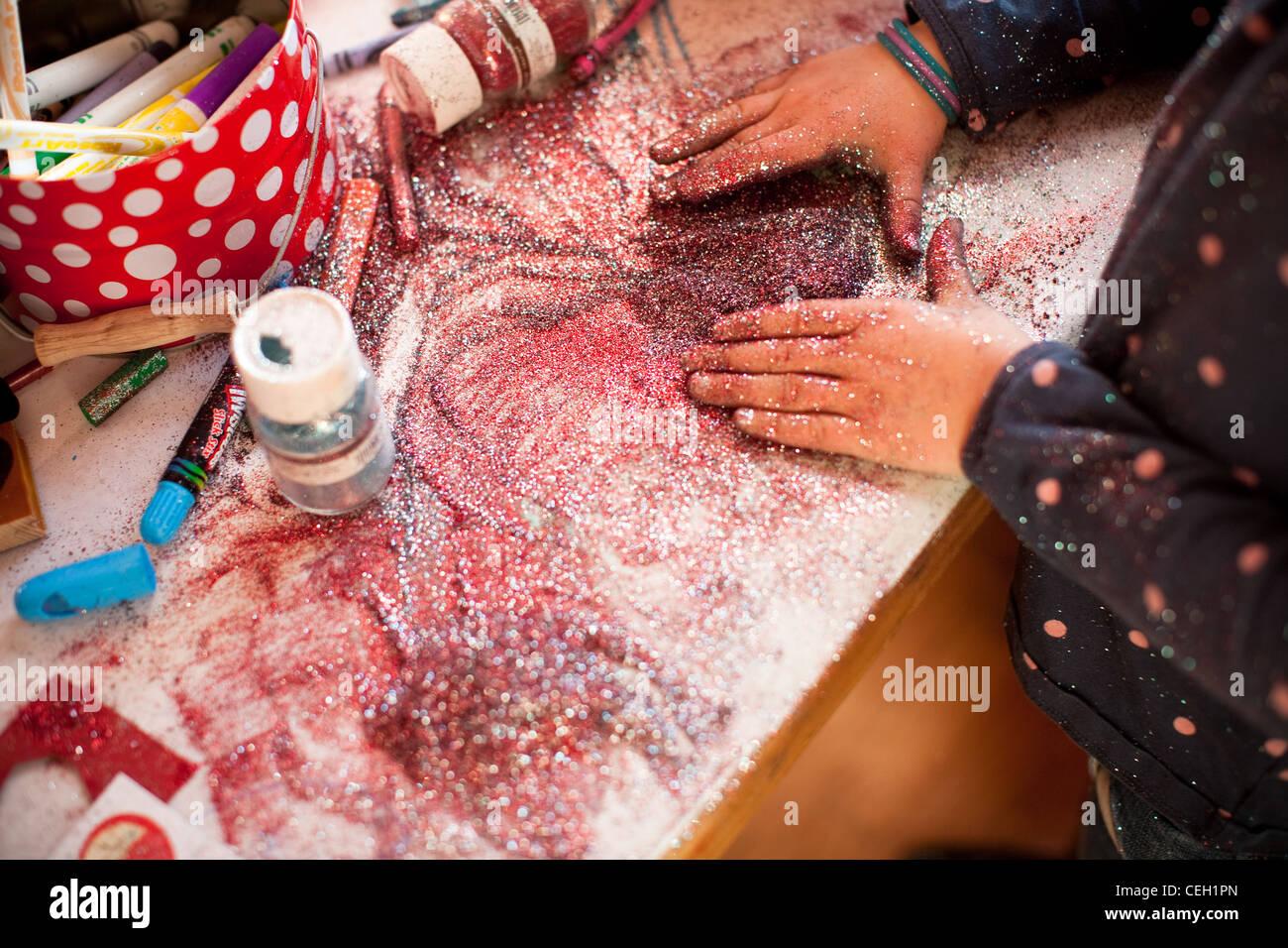 Sept ans, fille de jouer avec un tas de violet et rose glitter valentine lors d'un projet artistique, United Photo Stock