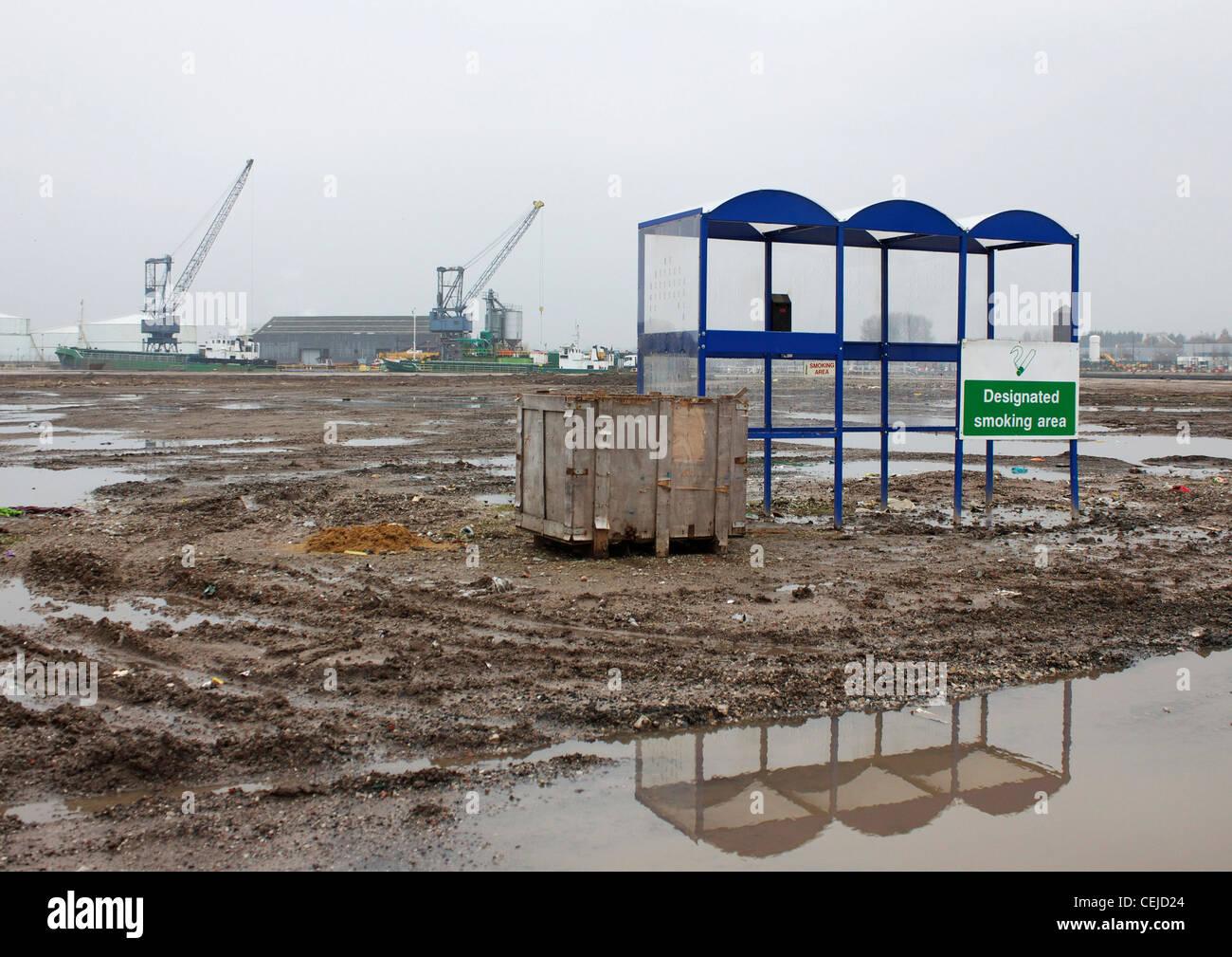 Un abri pour fumeurs tout seul dans un désert de boue et de flaques d'eau, Trafford Park, Manchester, Angleterre Photo Stock