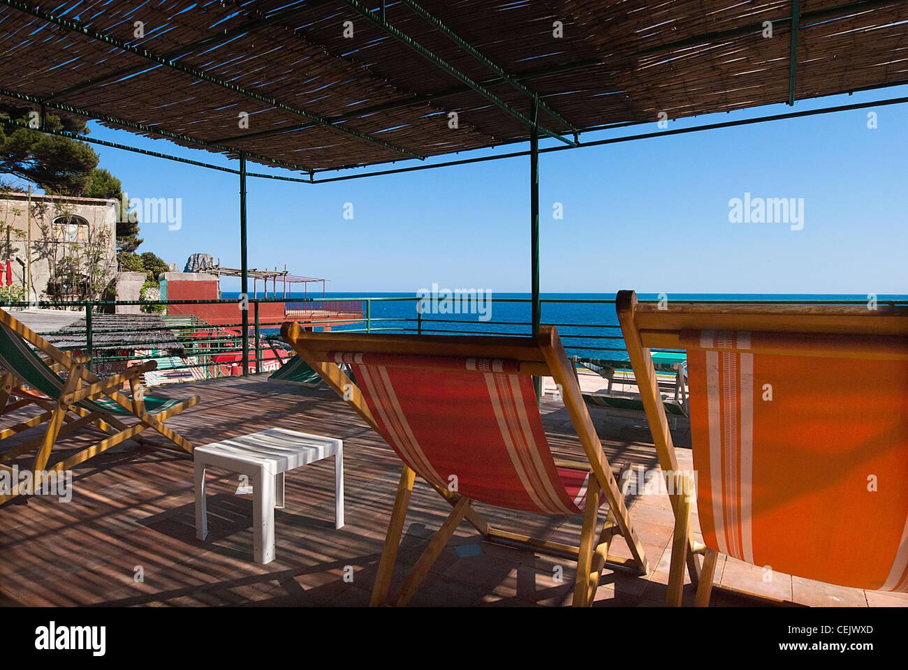 des chaises vides sur terrasse, sous l'auvent au beach club capri