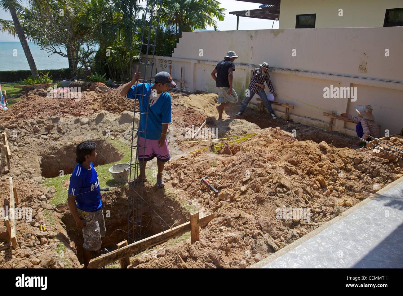 Ouvriers birmans creuser des trous pour construire une petite extension à Phuket, Thaïlande Photo Stock