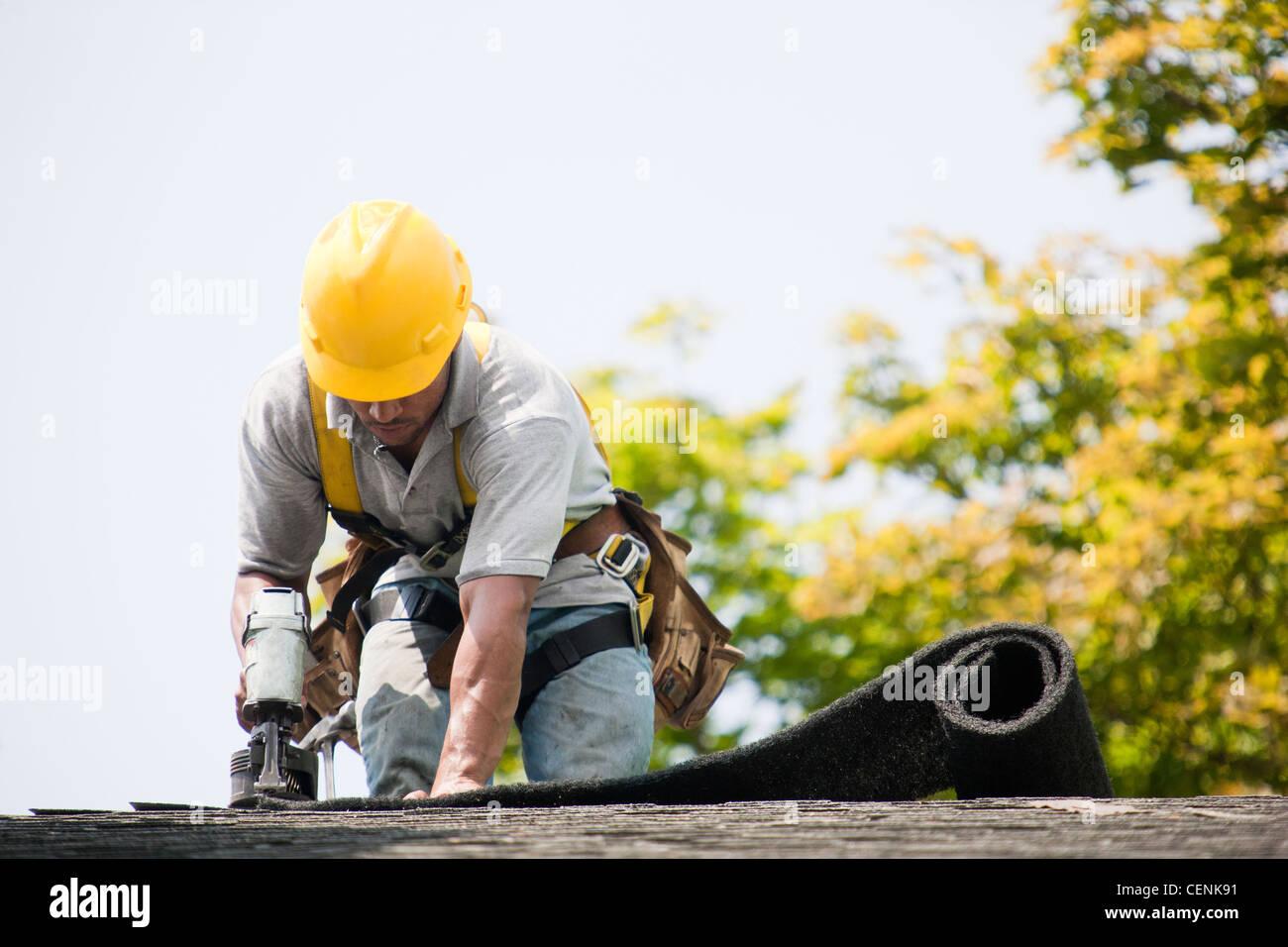 Couvreur travaillant sur un nouveau toit de bardeaux Photo Stock